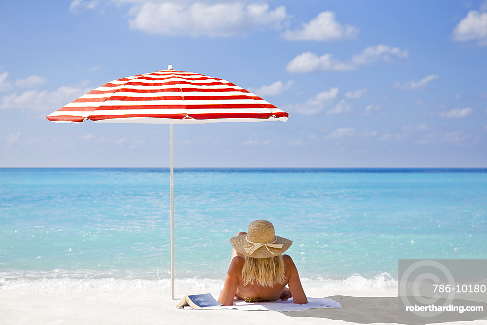 Woman relaxing on sunny beach with book under striped beach umbrella, Greece