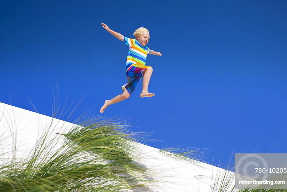 Exuberant boy jumping for joy over sand dune beach hill