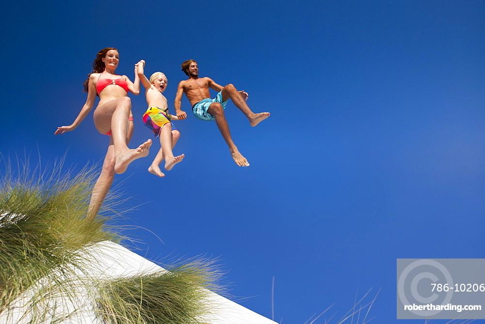 Family jumping over sand dune beach hill
