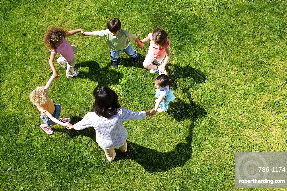 Teacher playing game of ring-a-ring-o'roses with children (3-5) on grass, overhead view