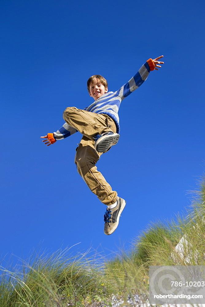 Exuberant boy jumping for joy over sand dune beach grass