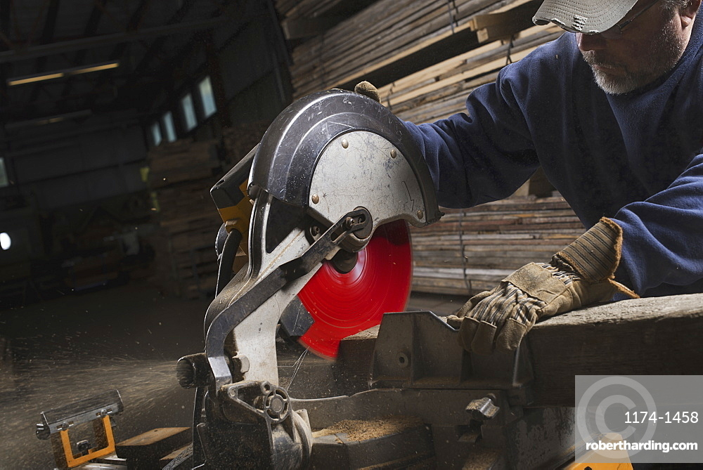 A reclaimed lumber workshop. A man in protective eye goggles using a circular saw to cut timber, Woodstock, New York, USA