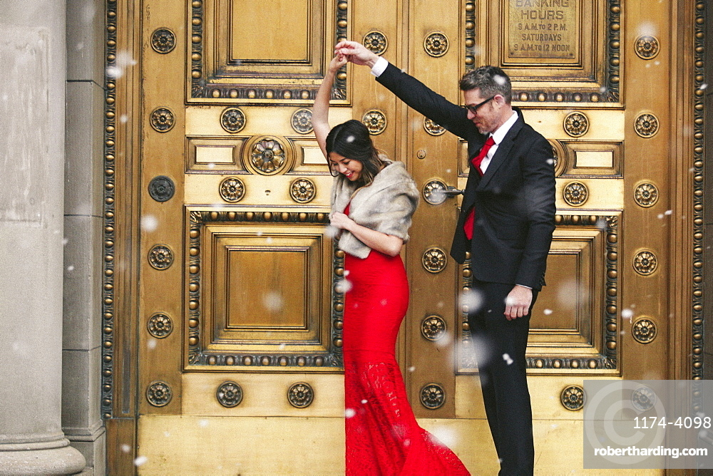 A woman in a long red evening dress with fishtail skirt and a fur stole, and a man in a suit dancing on the steps of a building.