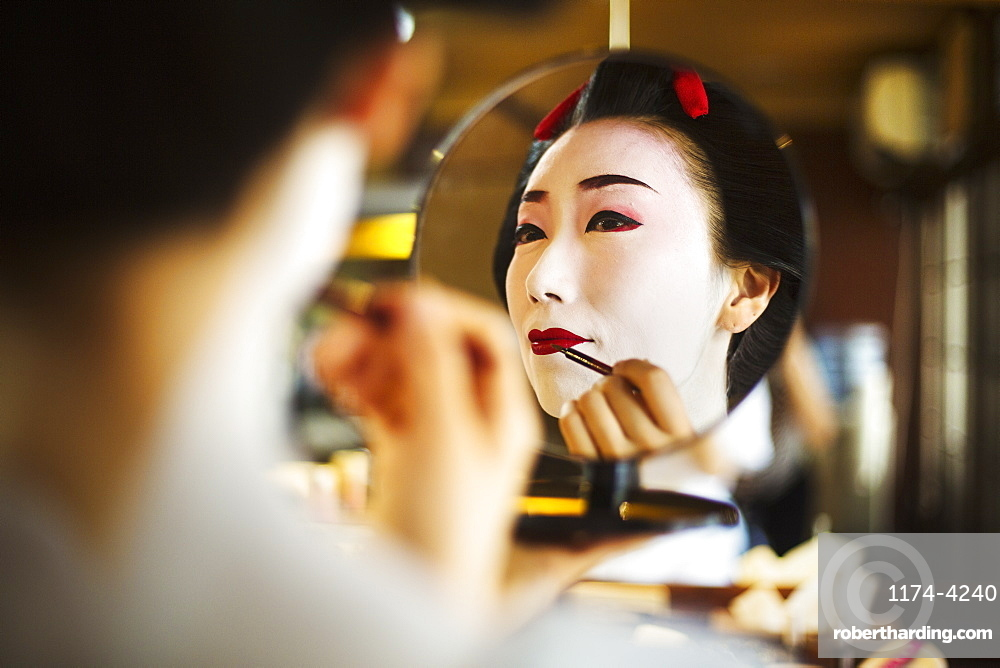 A modern geisha or maiko woman being prepared in traditional fashion, with  white face makeup