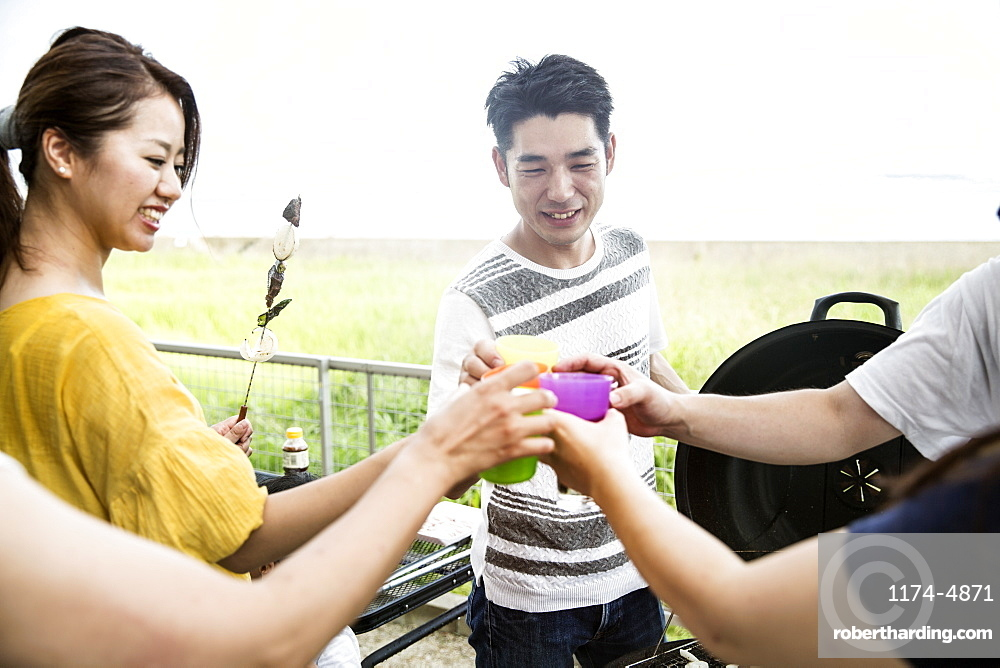 Group of Japanese men and women standing outdoors, toasting with plastic beakers, Kyushu, Japan