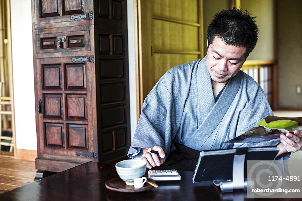 Japanese man wearing kimono sitting on floor in traditional Japanese house, using calculator and digital tablet, Kyushu, Japan