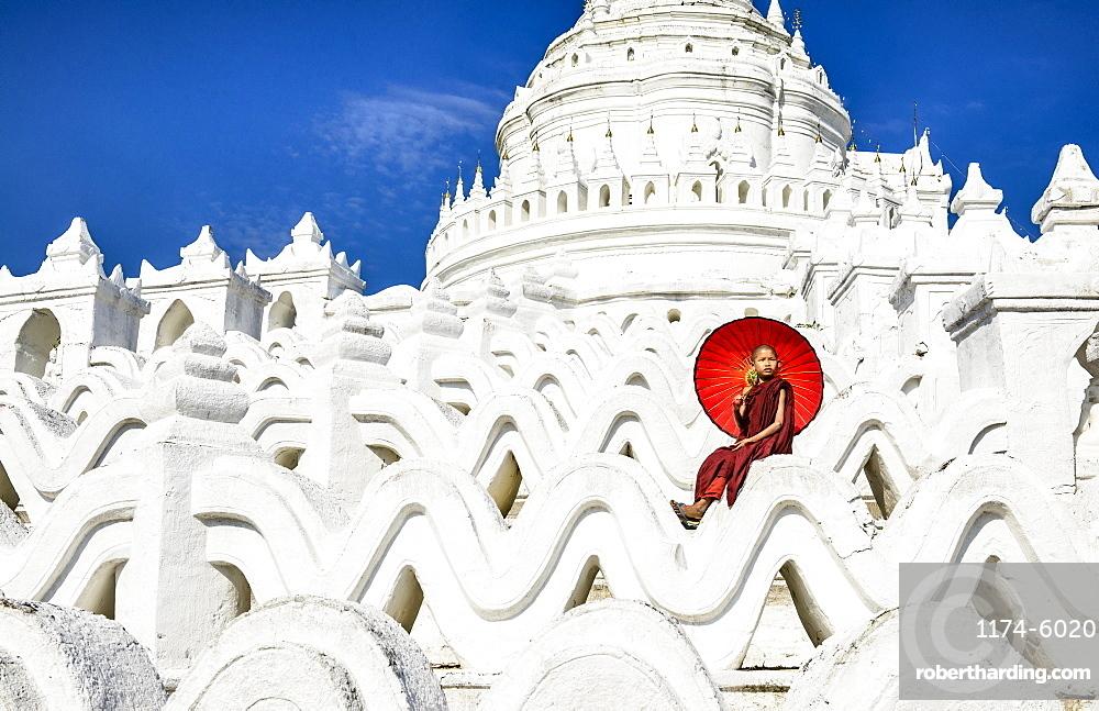 Asian woman sitting on temple walls, Mingun, Saigang, Myanmar