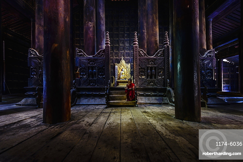 Monk siting by ornate shrine in temple