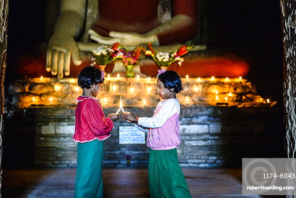 Asian girls lighting candles in Buddhist temple