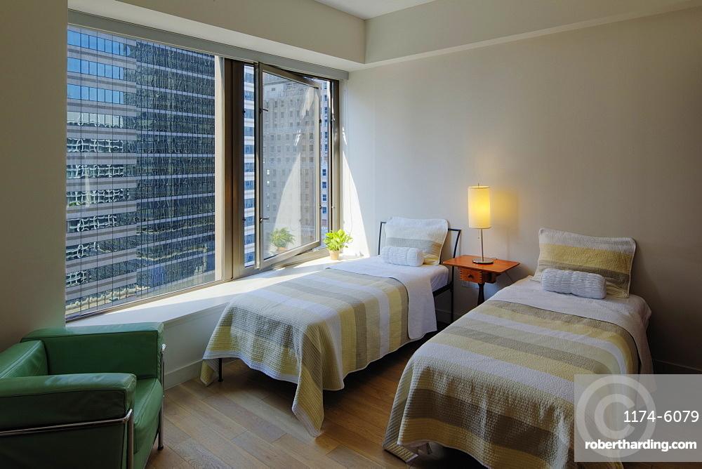Twin beds in bedroom overlooking city skyscraper