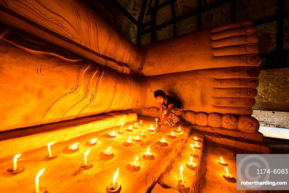 Asian girl lighting prayer candles in Buddhist temple