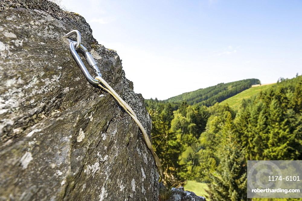 Carabiner on hook in steep rock face