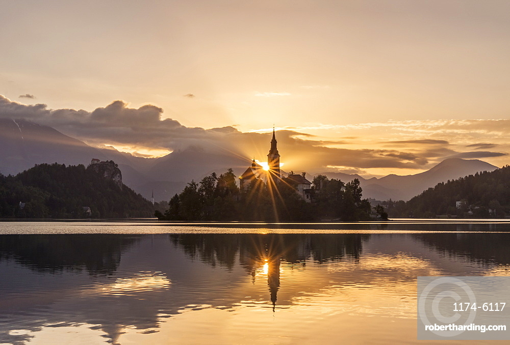 Sunrise over church tower reflected in still lake, Bled, Upper Carniola, Slovenia