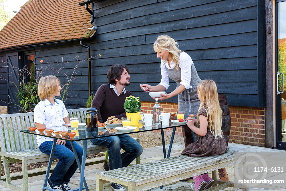 Caucasian family eating breakfast in backyard