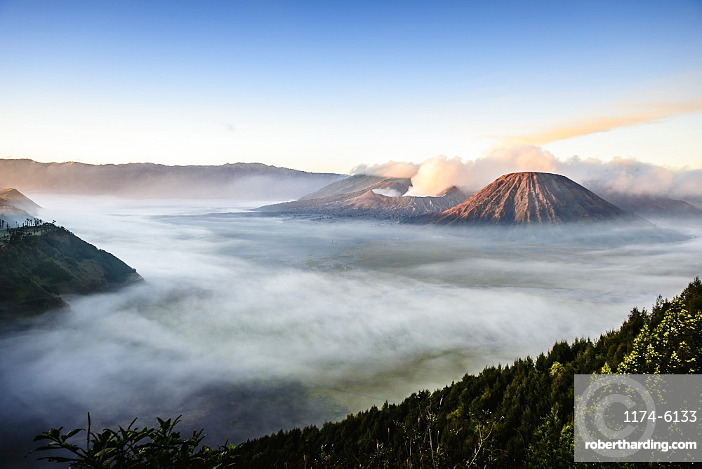 High angle view of clouds under smoking volcano