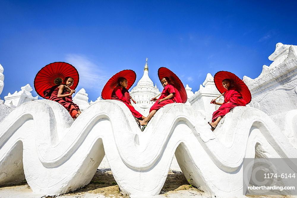 Asian monks sitting under umbrellas at historic temple, Mingun, Mandala, Myanmar