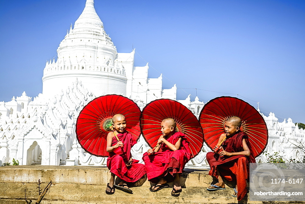 Asian monks sitting under umbrellas near historic temple, Mingun, Mandala, Myanmar