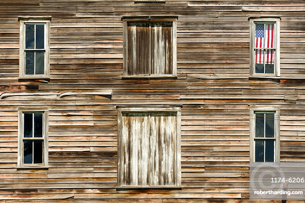 Wooden house exterior with American flag in window