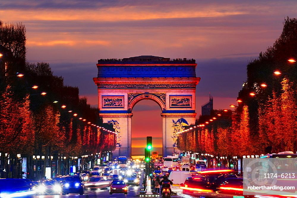Arc de Triomphe over traffic at night, Paris, Ile-de-France, France