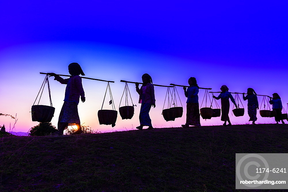 Silhouette of people carrying baskets under sunset sky, Myanmar, Burma