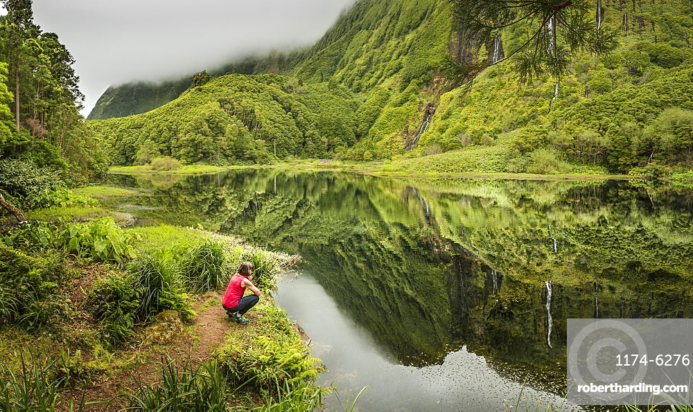 Hiker crouching at still lake in remote mountains, Faja Grande, Flores, Portugal