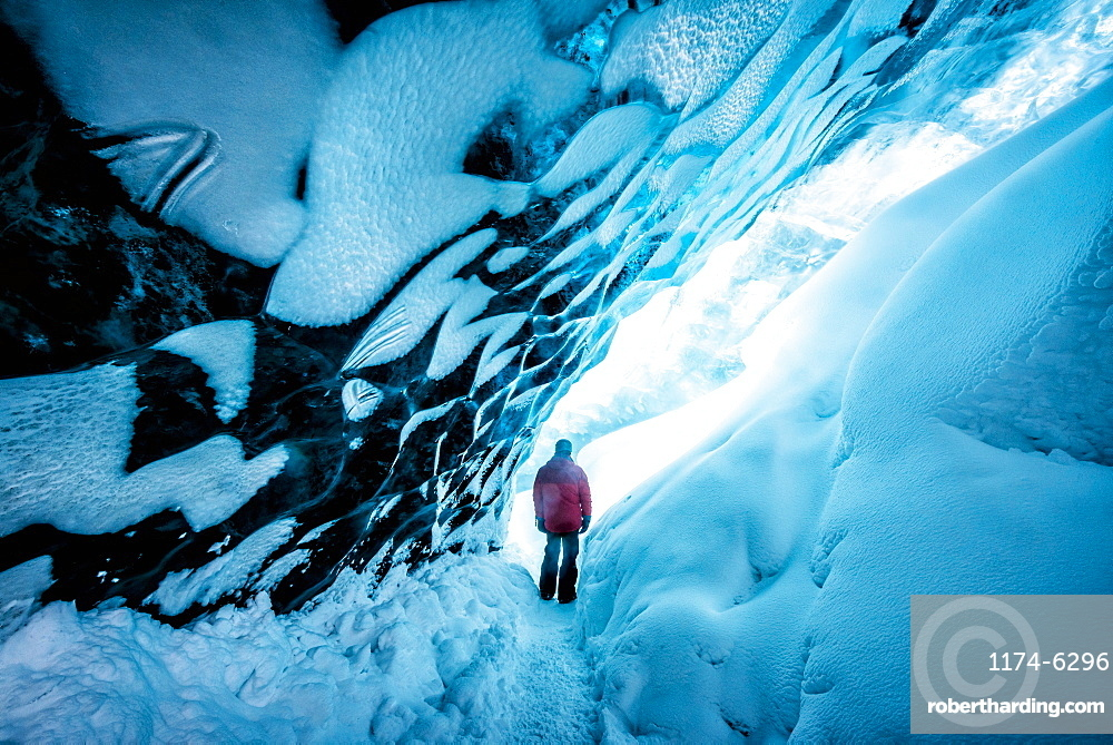 Hiker walking in ice cave, Jokulsarlon, Iceland