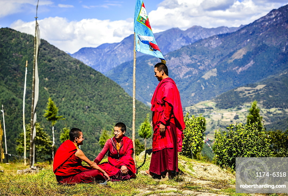 Asian monks with flag on remote hilltop, Bhutan, Kingdom of Bhutan