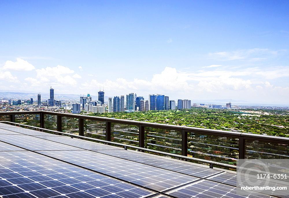 Solar panels and Manila cityscape under blue sky, Philippines, Manila, Philippines