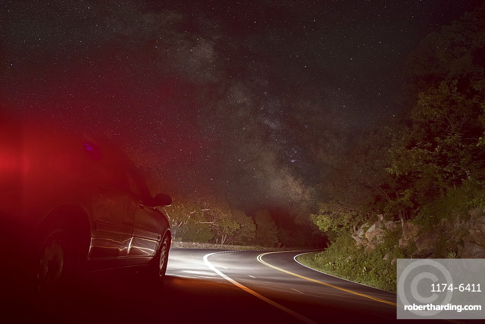 Car on winding road under starry sky, Front Royal, Virginia, USA