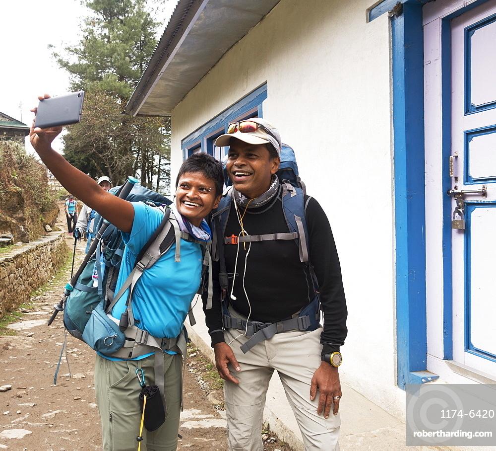 Tourists posing for cell phone selfie, Lukla, Khumbu, Nepal