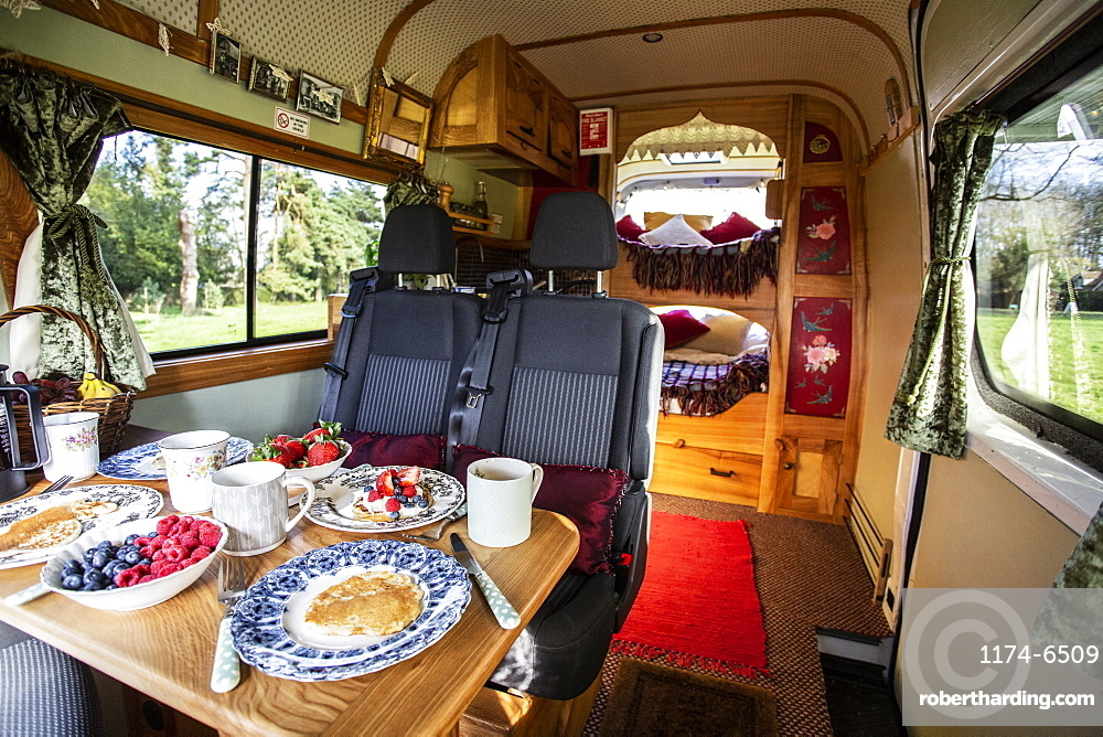 Interior view of camper van with breakfast on table, Oxfordshire, England
