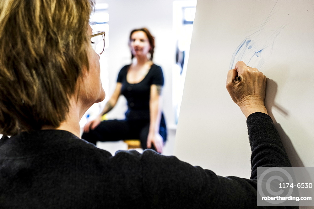 Close up of woman standing at easel, drawing human hand, artist's model sitting in the background. A life drawing class with a model, Oxfordshire, England