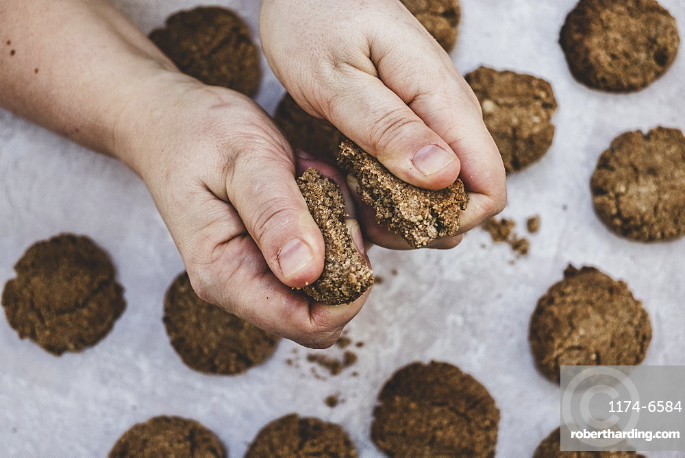 High angle close up of person breaking freshly baked chocolate cookie in half, England