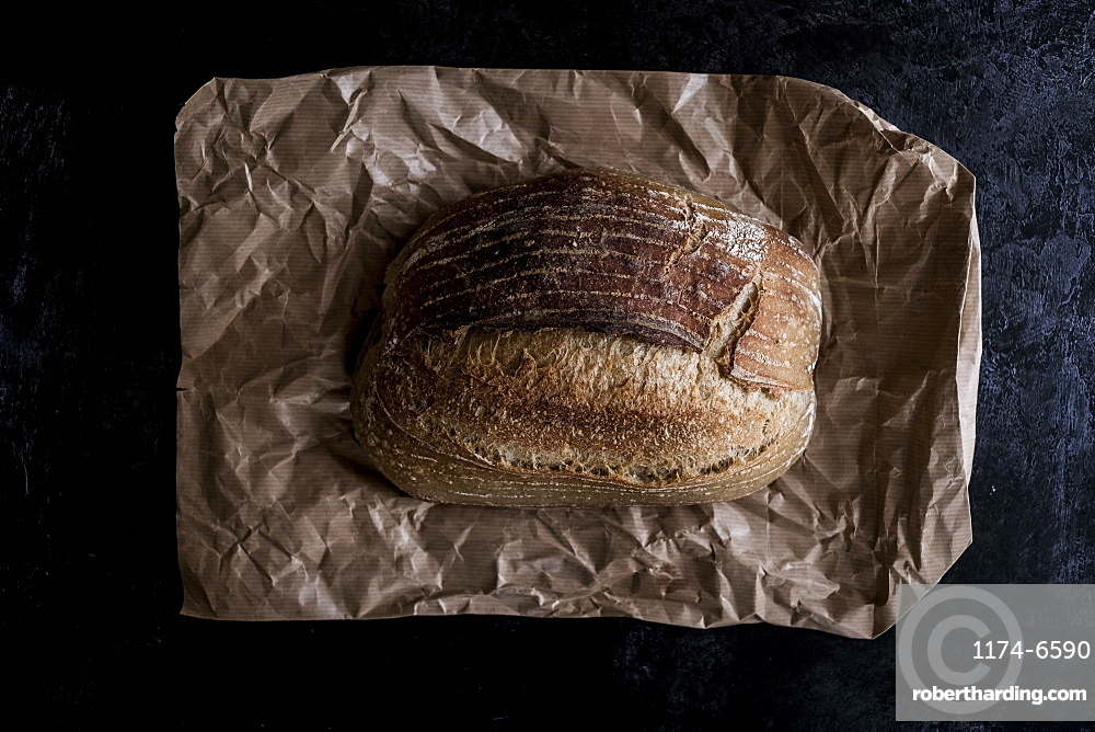 A fresh loaf of baked bread on a brown paper bag, England