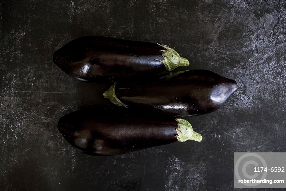 Three glossy purple aubergine egg plant vegetables on a grey slate background, England