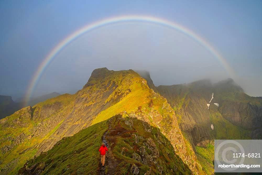 Man climbing towards a rainbow in the Lofoten Islands, Norway