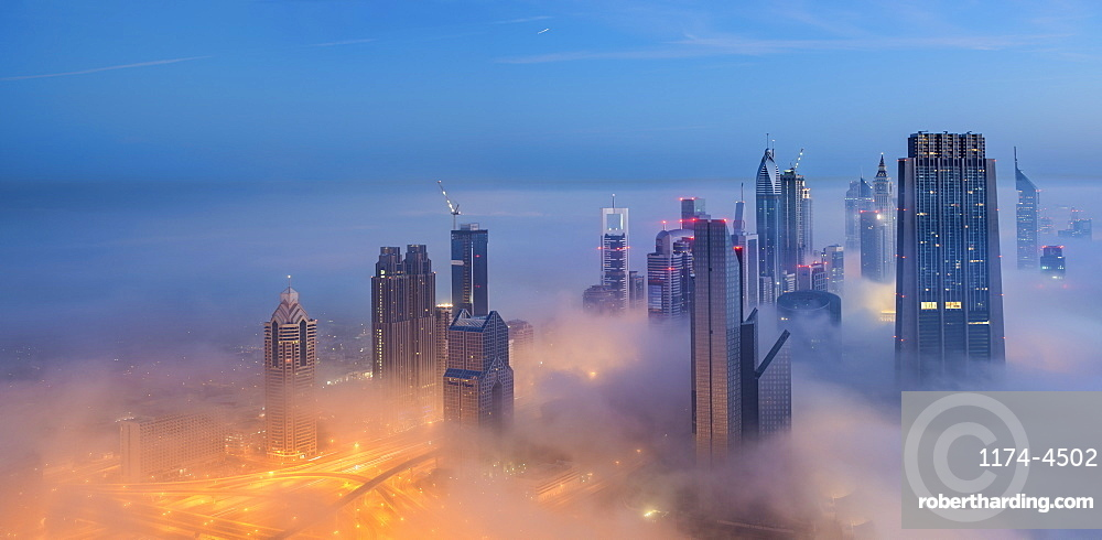 Cityscape with illuminated skyscrapers above the clouds in Dubai, United Arab Emirates at dusk, Dubai, United Arab Emirates
