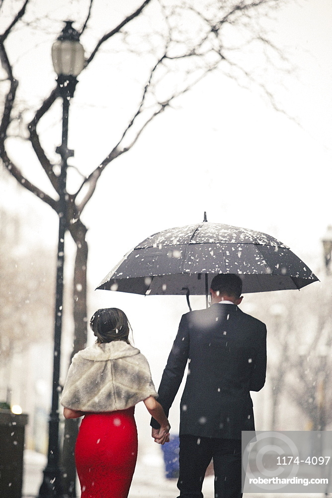 A woman in a long red evening dress and a man in a suit, walking through snow in the city.
