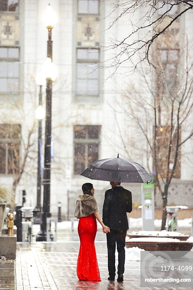 A woman in a long red evening dress with fishtail skirt and a fur stole, and a man in a suit, walking through snow in the city.