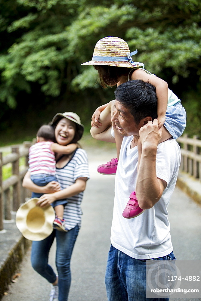 Japanese girl, smiling woman holding hat and man carrying toddler on his shoulders standing on wooden bridge, Kyushu, Japan