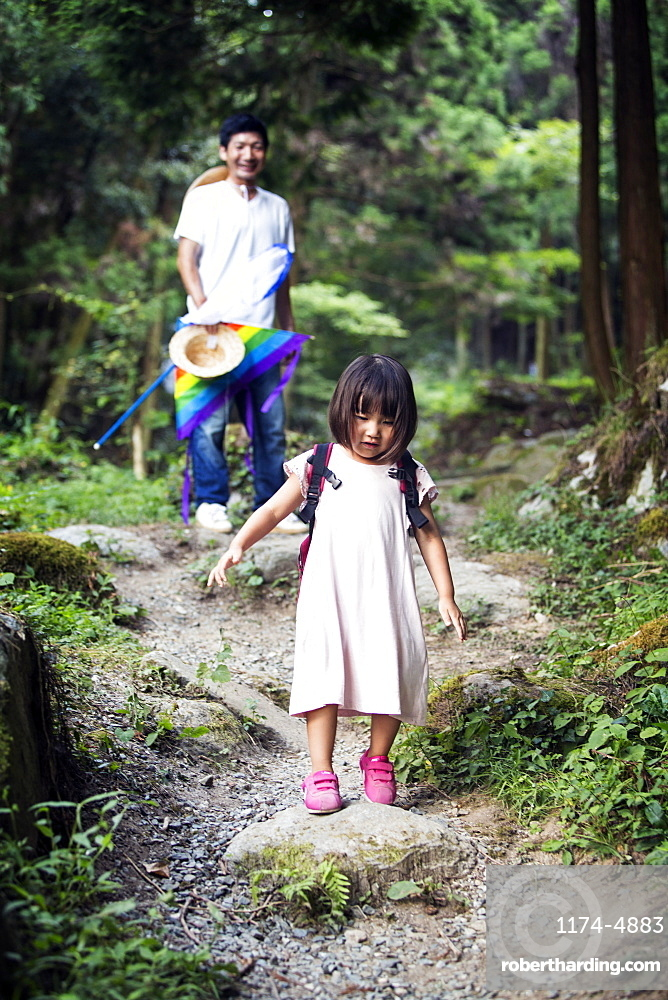 Japanese girl wearing pale pink sun dress and carrying backpack standing in a forest, man in the background, Kyushu, Japan