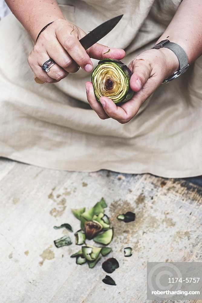 Close up of person peeling fresh artichoke with kitchen knife, Oxfordshire, England