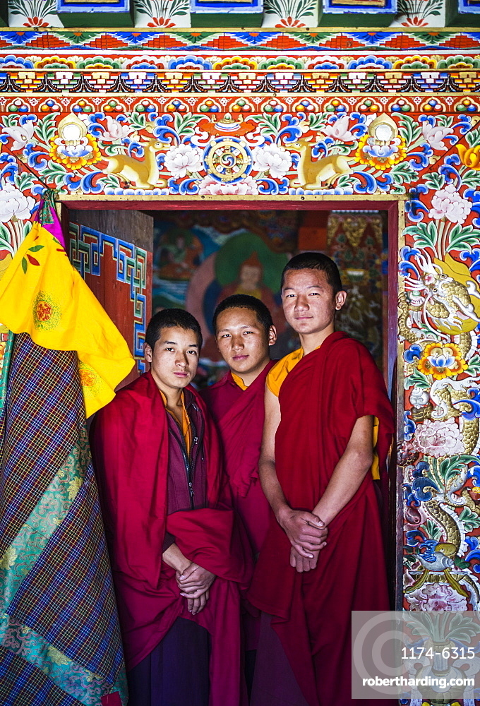 Asian monks standing in temple doorway, Bhutan, Kingdom of Bhutan