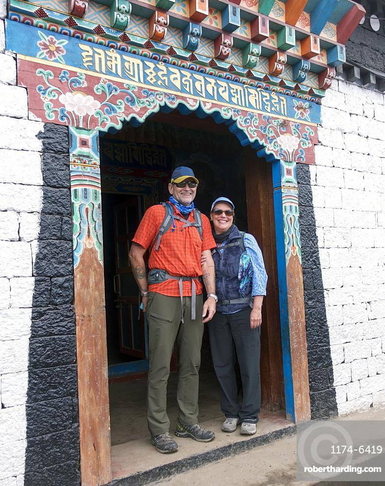 Caucasian couple standing in ornate doorway, Lukla, Khumbu region, Nepal