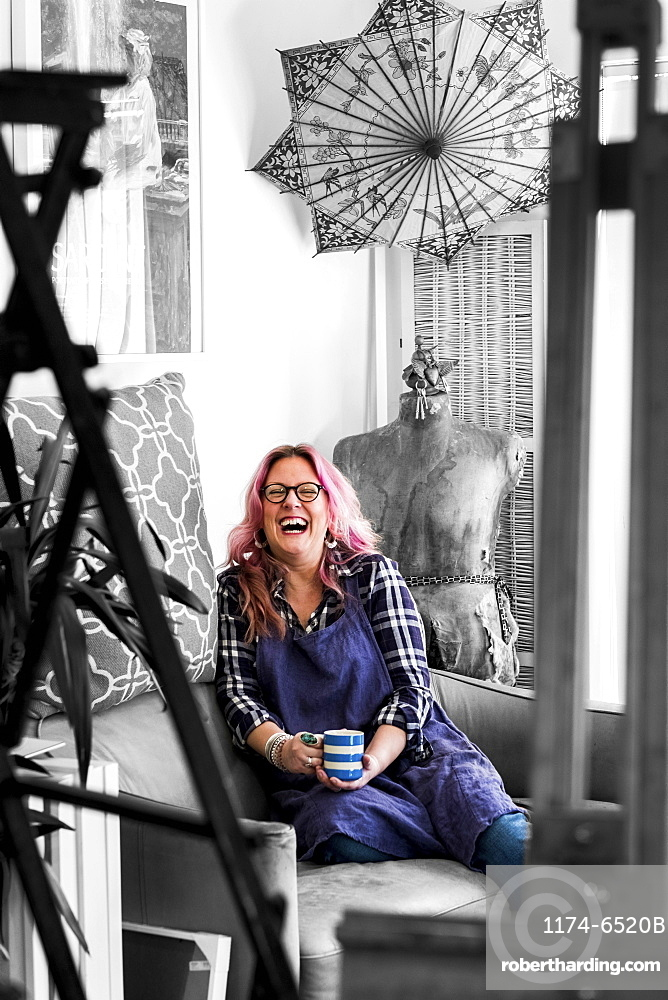 Laughing woman with long blond wavy hair with pink streaks sitting on a sofa, looking at camera, Oxfordshire, England
