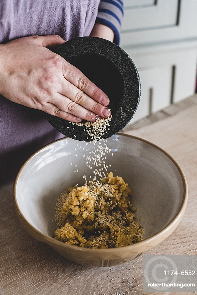 High angle close up of person adding sesame seeds to dough in a mixing bowl, England