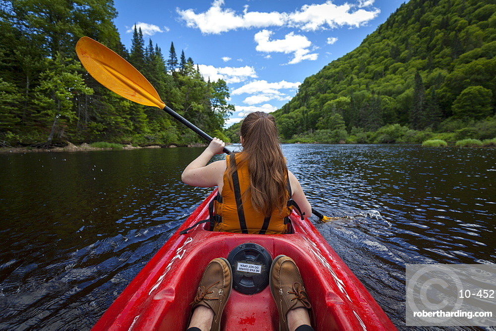 Young woman paddles down river | Stock Photo