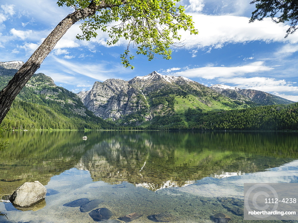 Snow-capped mountains reflected in the calm waters of Phelps Lake, Grand Teton National Park, Wyoming, United States of America, North America