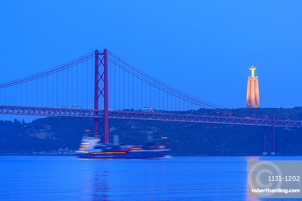 Container ship passing under the Bridge of 25 April and Almada Cristo Rei statue at sunset, Belem district, Lisbon, Portugal, Europe