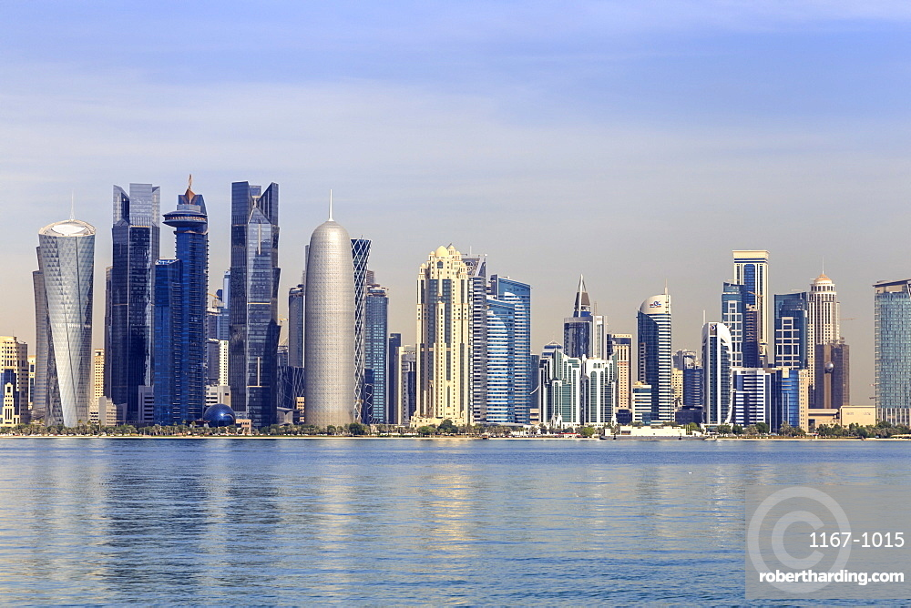 Modern city skyline of West Bay, across the calm waters of Doha Bay, from the Dhow Harbour, Doha, Qatar, Middle East